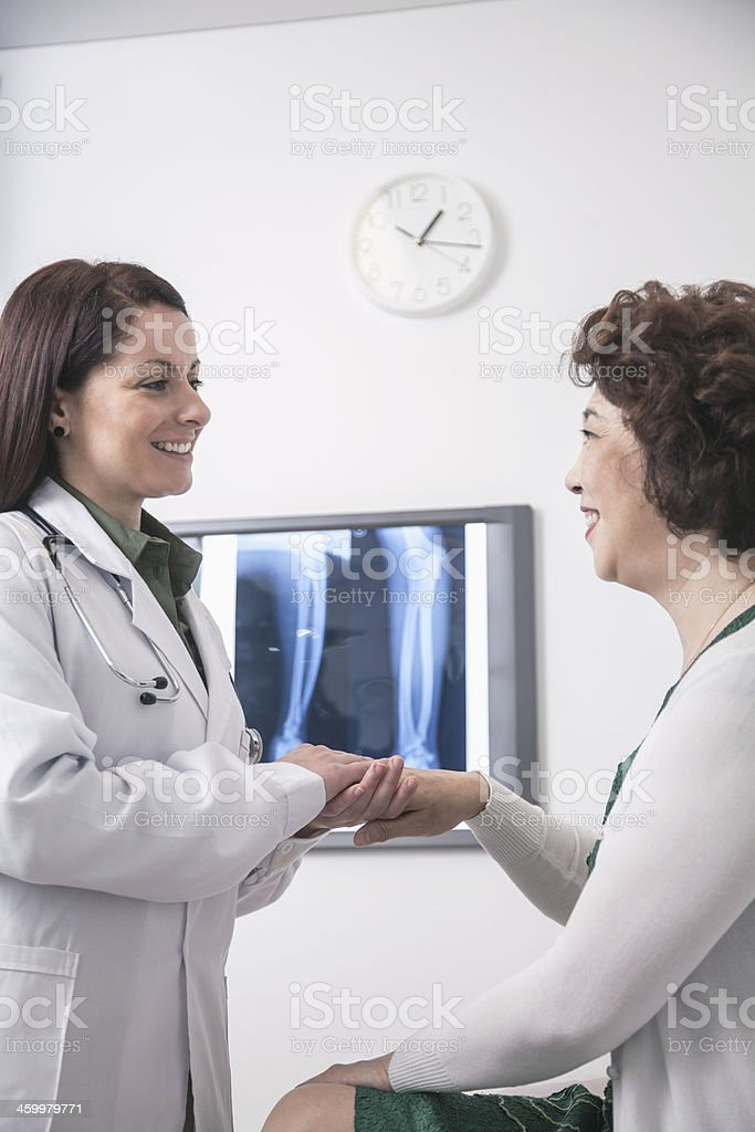 Young female doctor holding the hands of a patient royalty-free stock photo