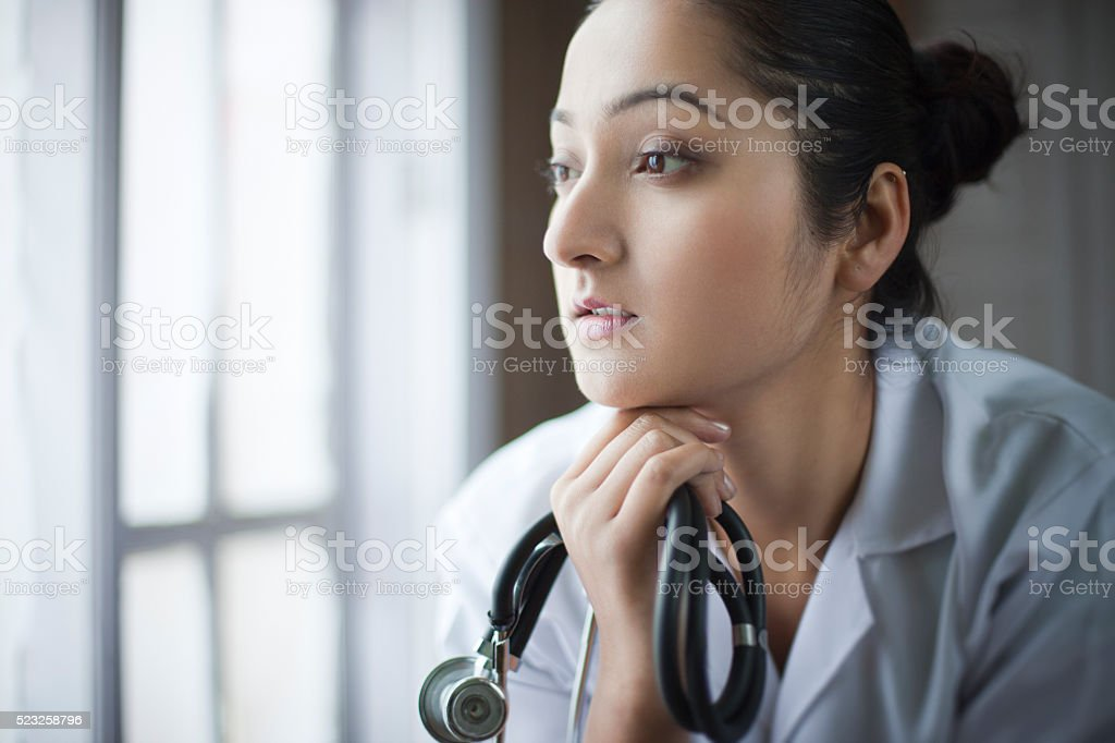 Young female doctor looking at view near window and thinking. stock photo