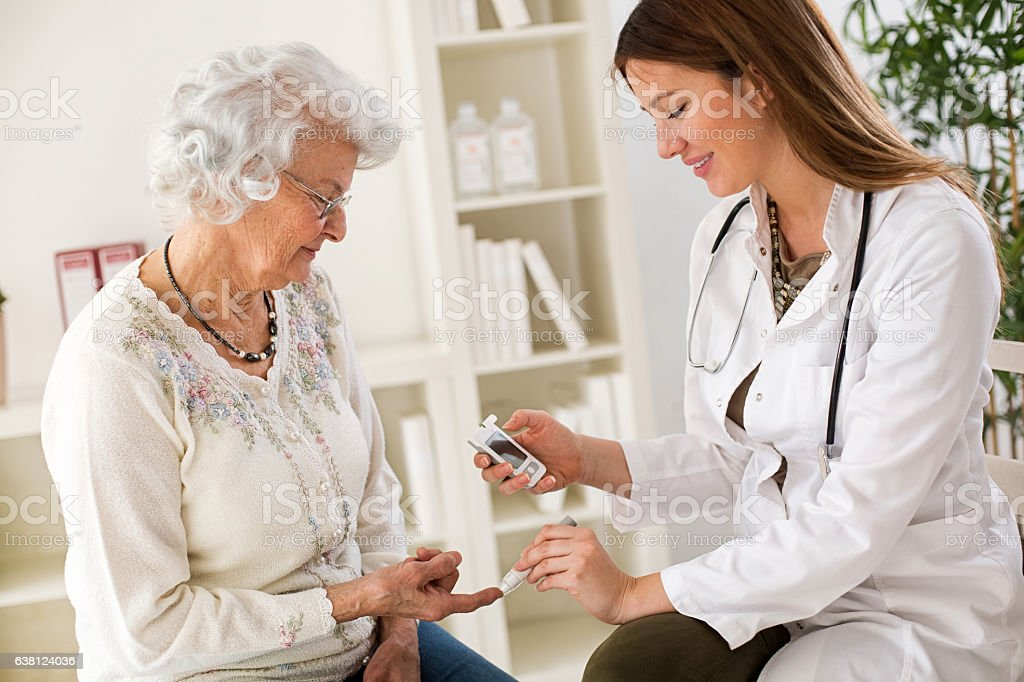 Young female doctor making diabetes blood test on senior woman stock photo