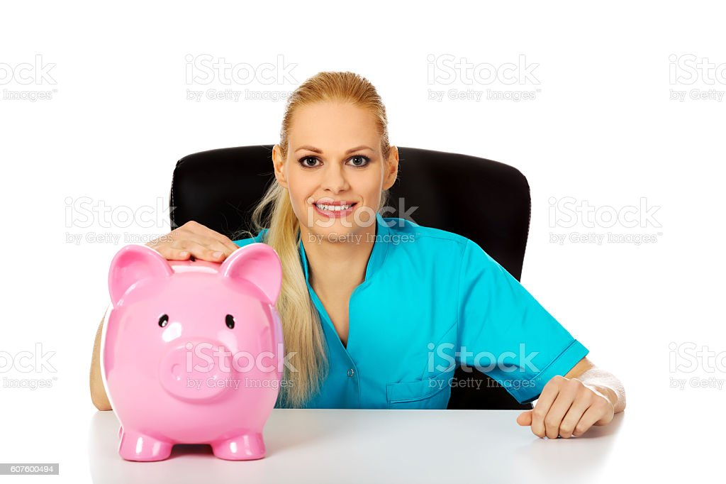 Young female doctor or nurse sitting behind the desk stock photo