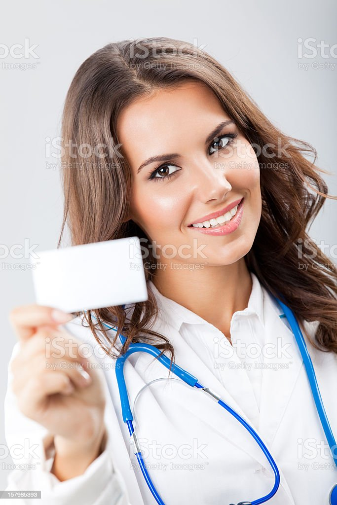 Young female doctor showing blank business card royalty-free stock photo