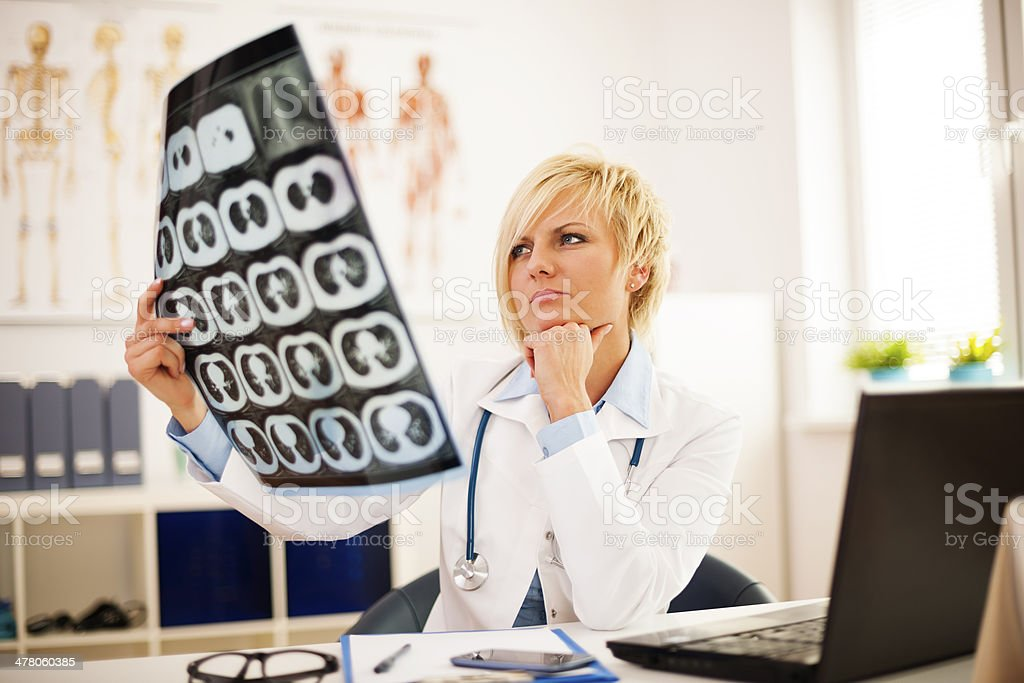 Young female doctor studying x-ray image royalty-free stock photo