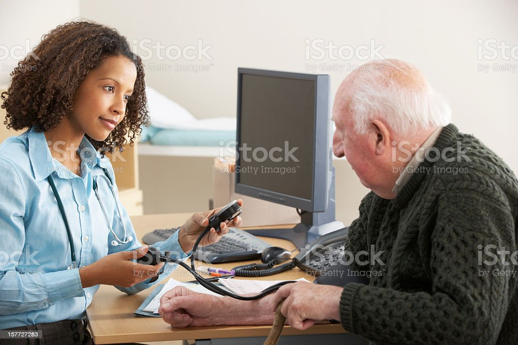 Young female Doctor taking senior man's blood pressure stock photo