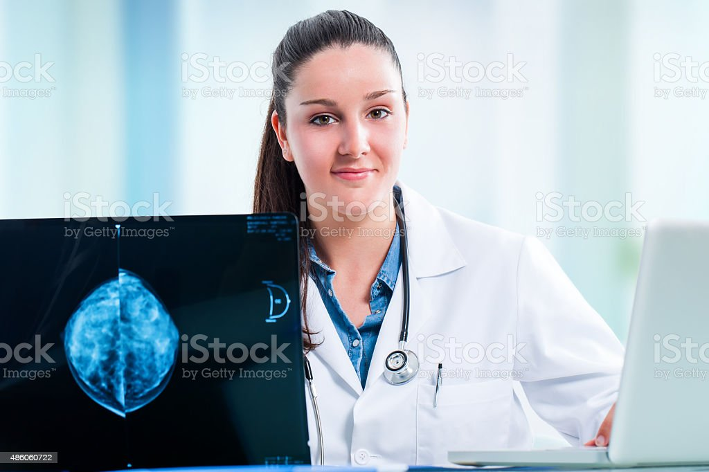 Young female doctor with x ray and laptop at desk. stock photo