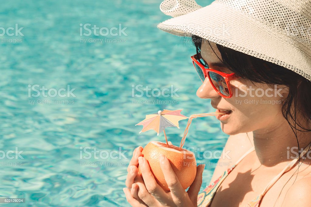 Young female drinking grapefruit juice next to the swimming pool stock photo