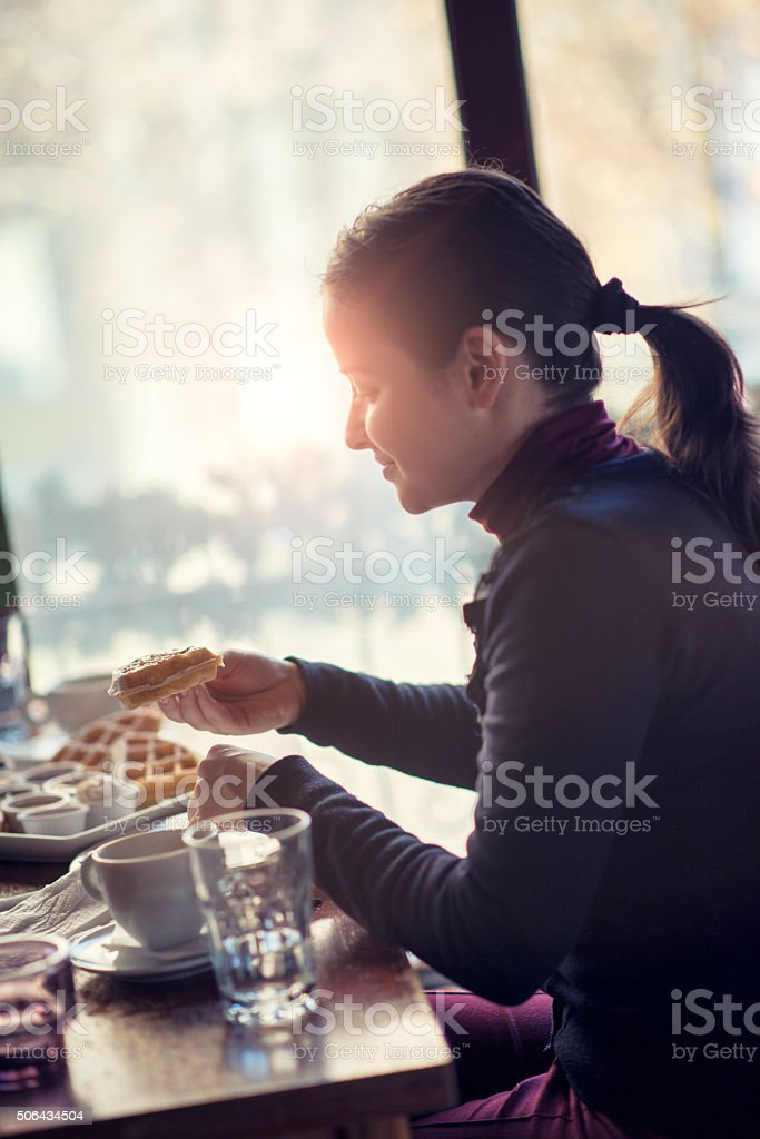 Young Female Eating Waffles for Breakfast at the Restaurant stock photo