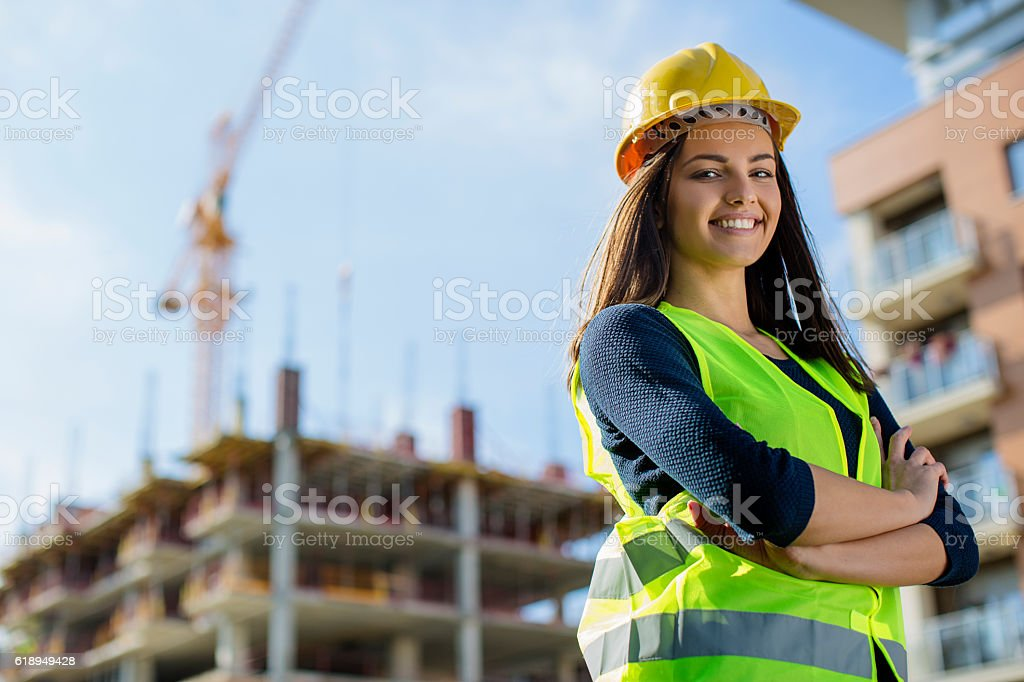 Young female engineer smiling at construction site stock photo