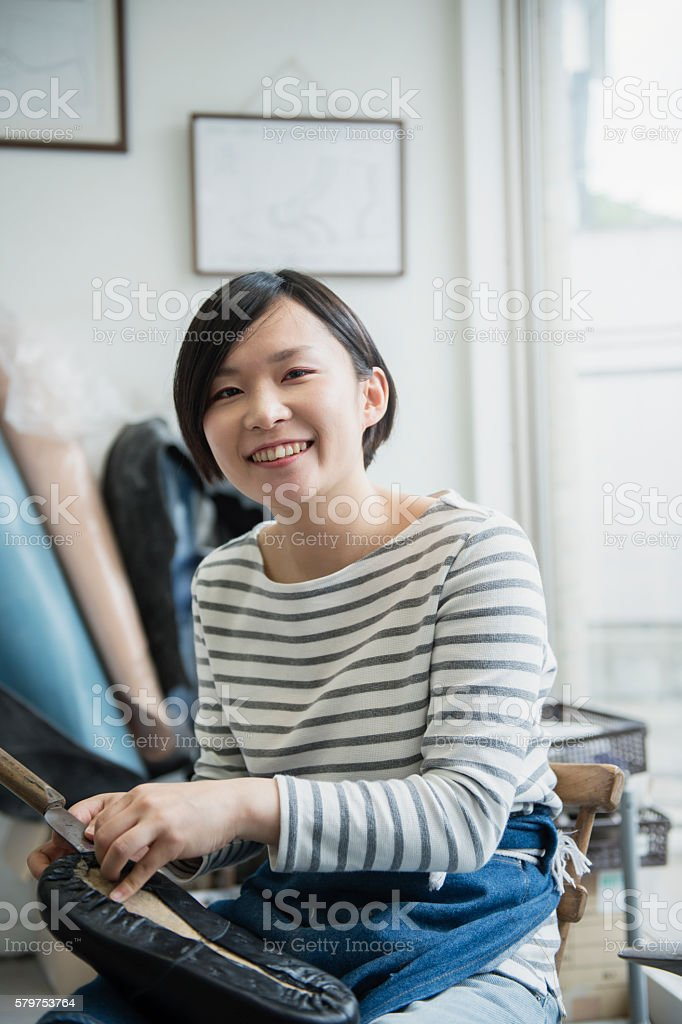 Young female entrepreneur in her shoe making studio stock photo