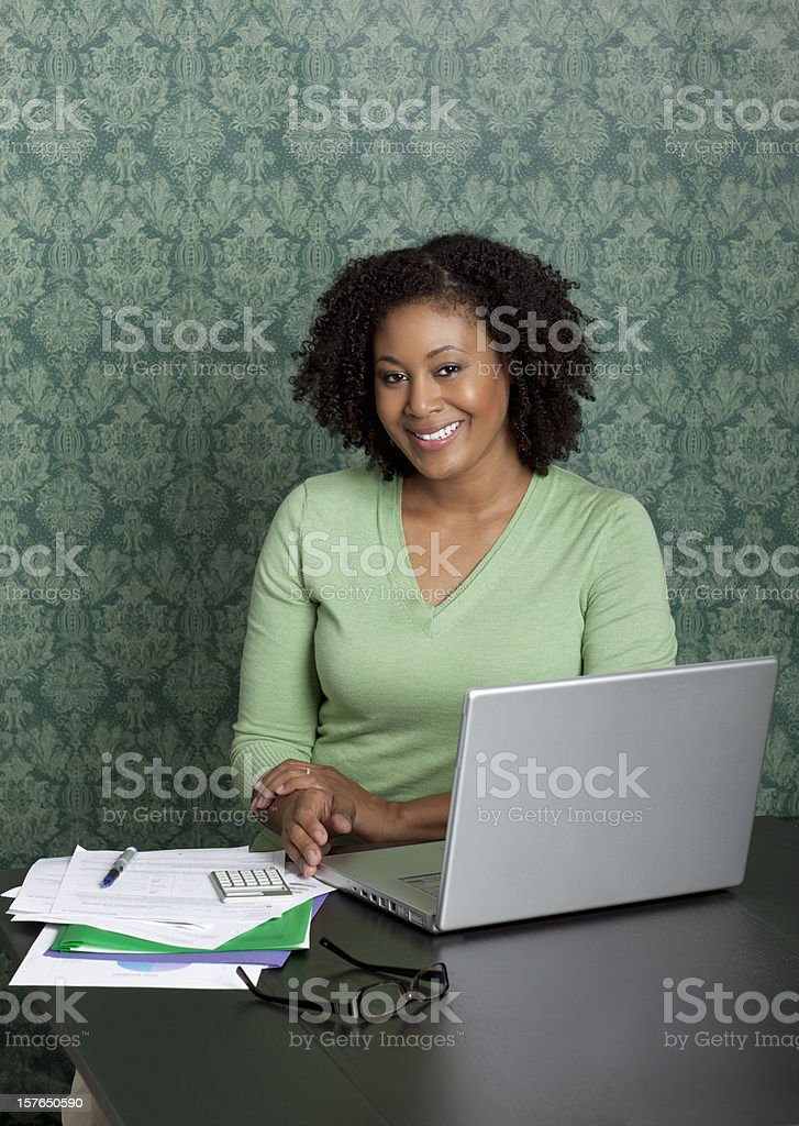 Young female executive sitting with laptop at desk royalty-free stock photo