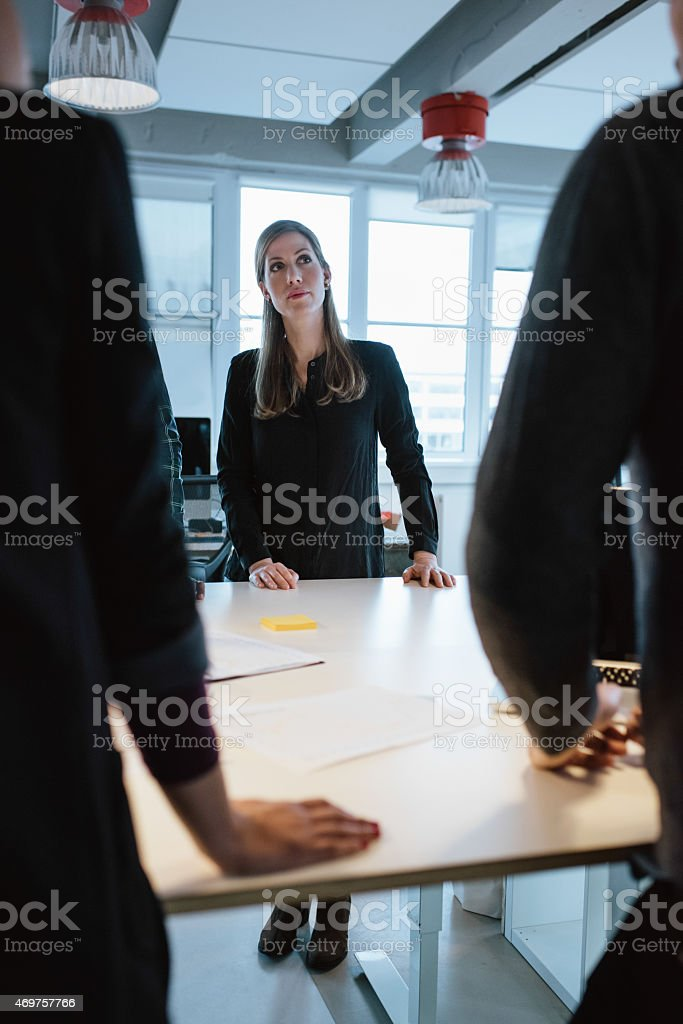 Young female executive with colleagues around a table stock photo