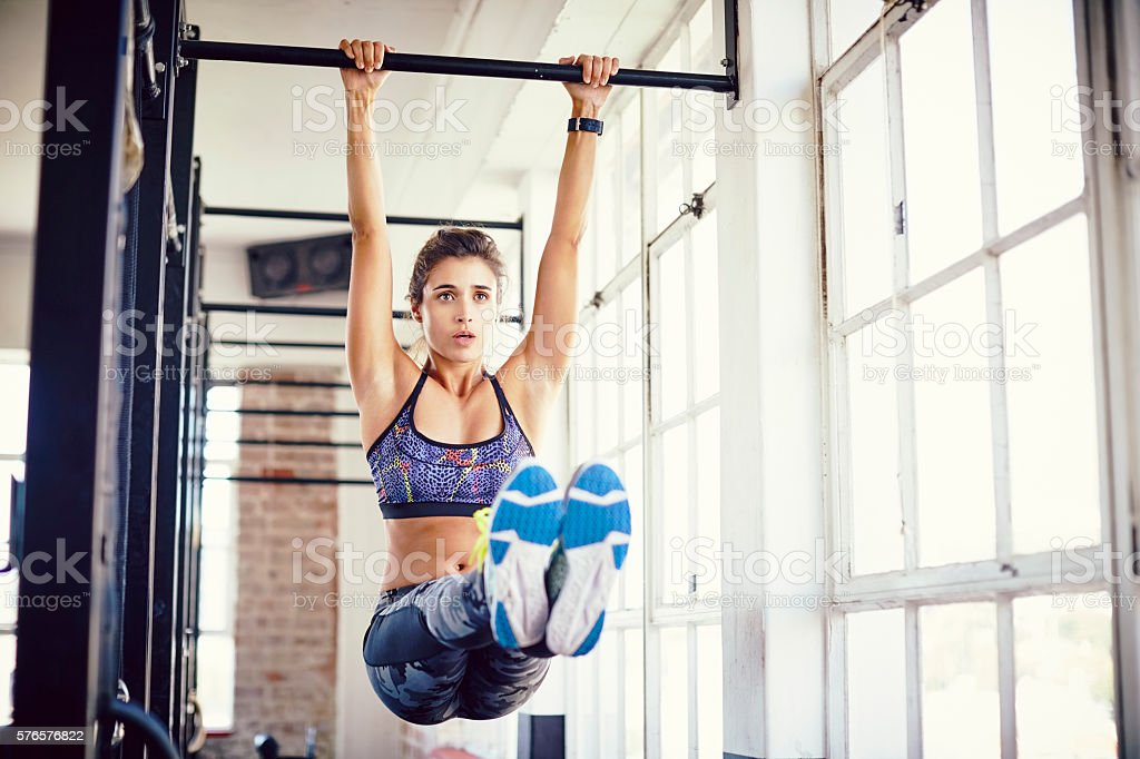 Young female exercising on pull-up bar in gym stock photo