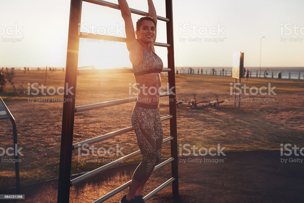 Young female exercising on wall bars outdoors stock photo