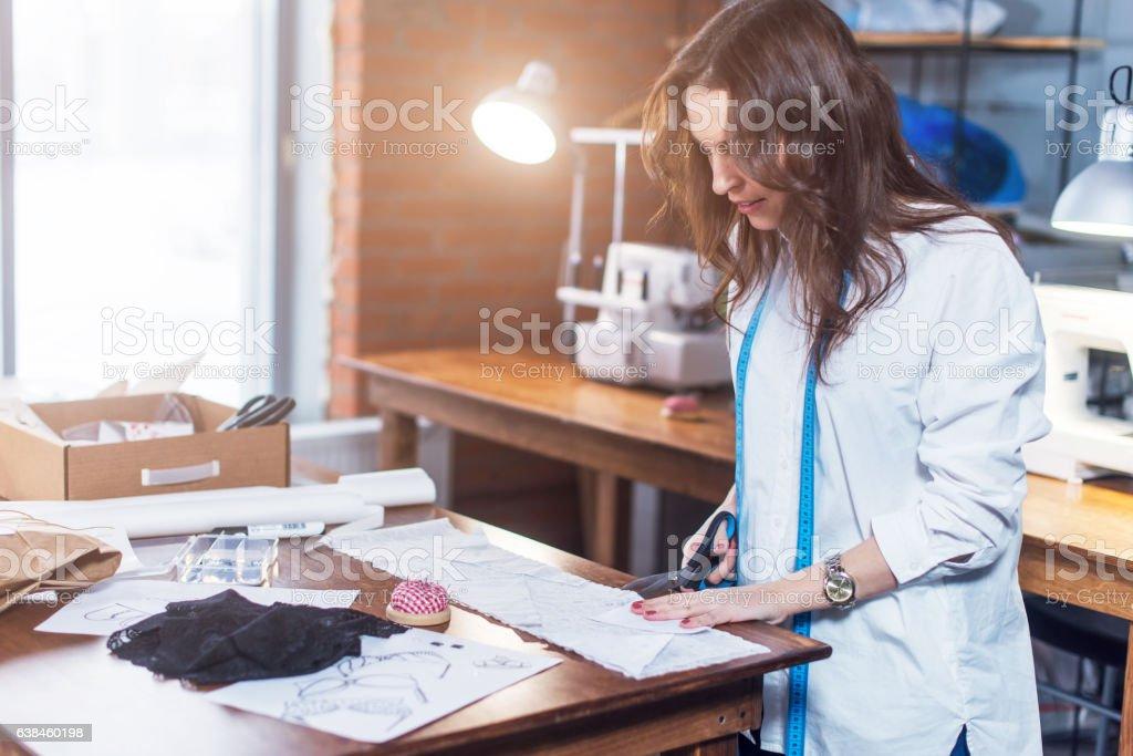 Young female fashion designer cutting fabric with scissors in studio stock photo