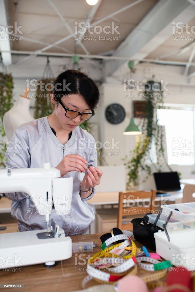 Young female fashion designer threading a needle stock photo