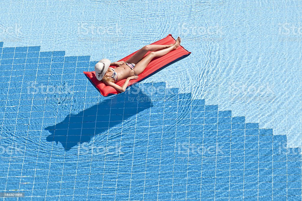 Young female floating in a swimming pool stock photo