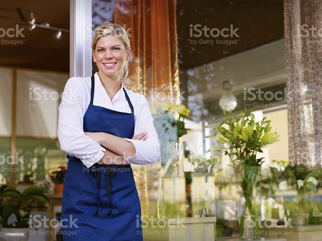Young female florist smiling in flower shop royalty-free stock photo