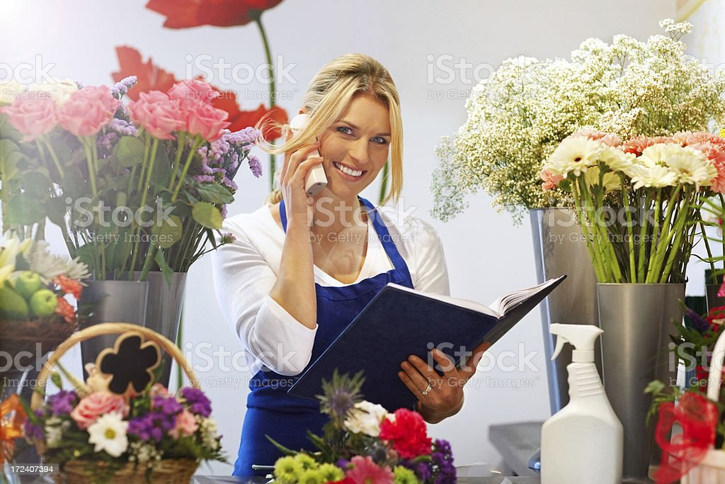 Young female florist taking order on telephone royalty-free stock photo