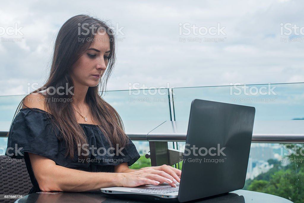 Young female freelancer dressed in black working on a project stock photo