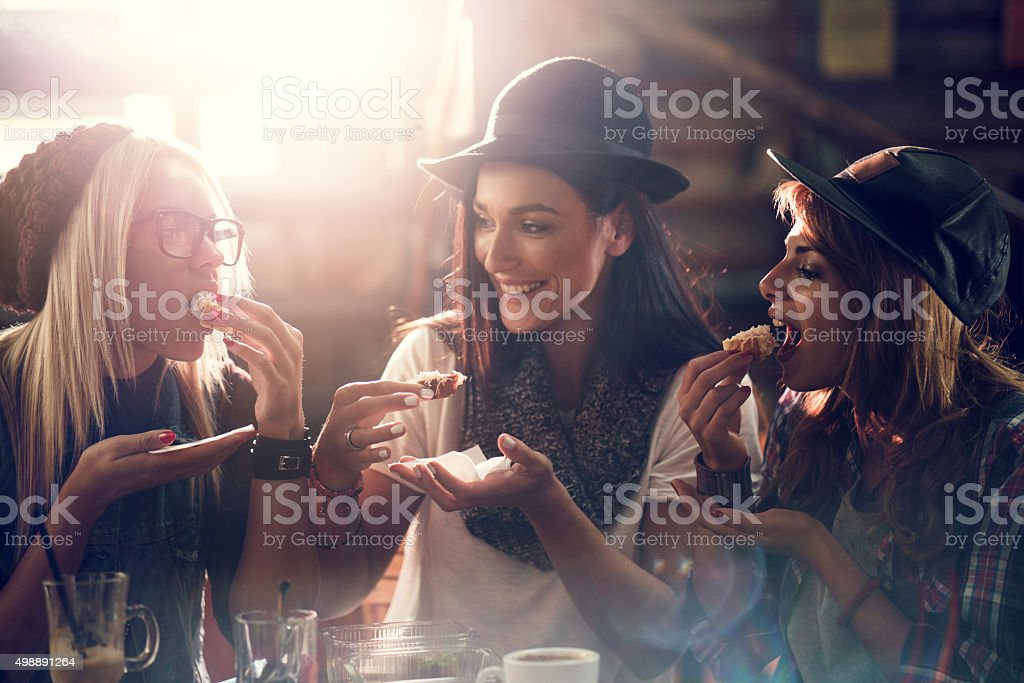 Young female friends having a snack in a cafe. stock photo