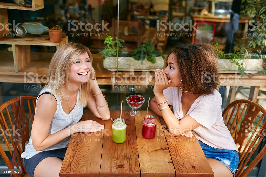 Young female friends having private gossips at cafe stock photo