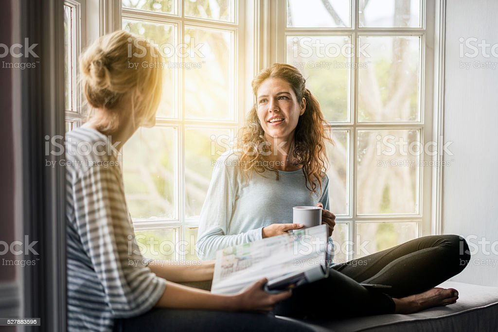 Young female friends talking on window sill stock photo