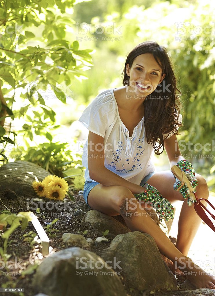 Young female gardner relaxing holding a rake and trowel royalty-free stock photo