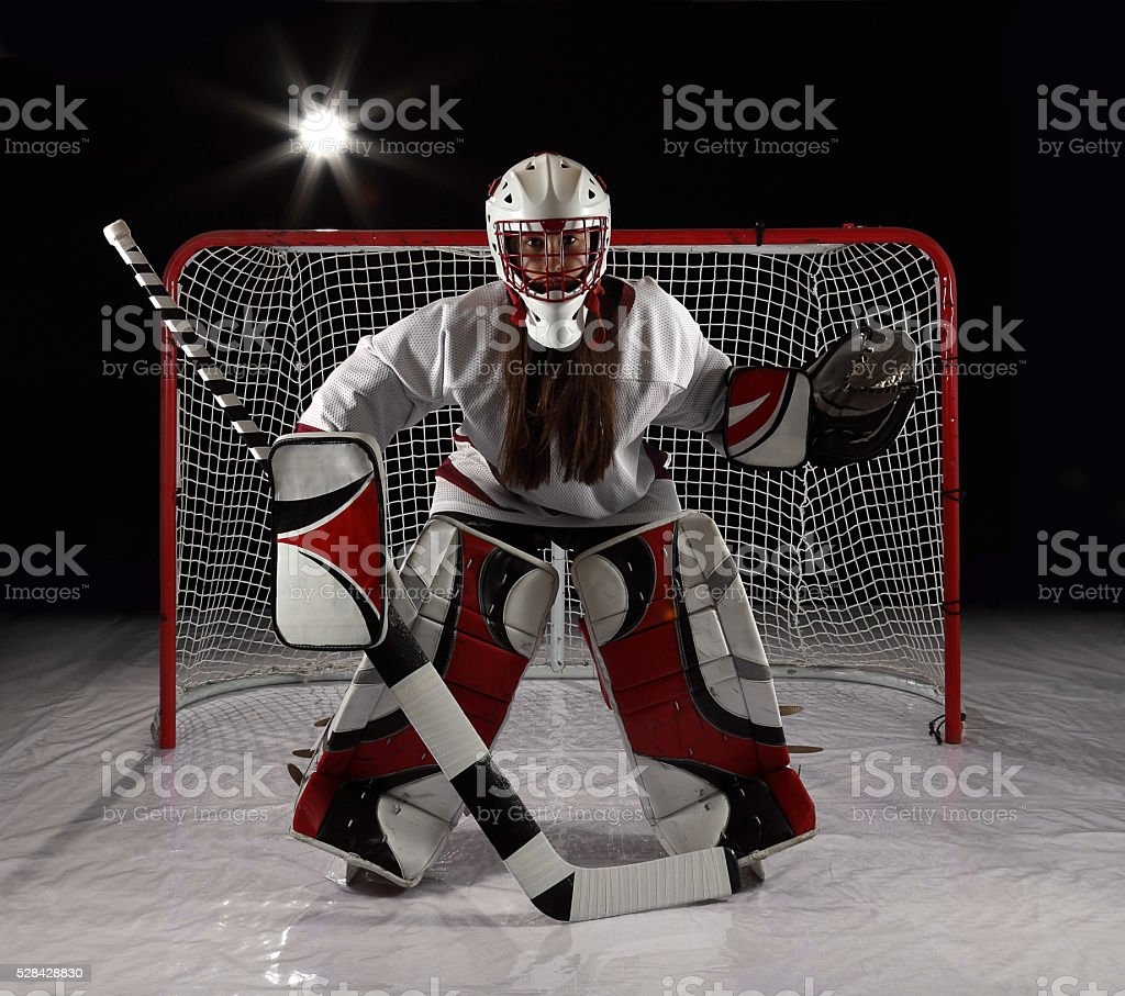 Young female goaltender in white jersey. stock photo