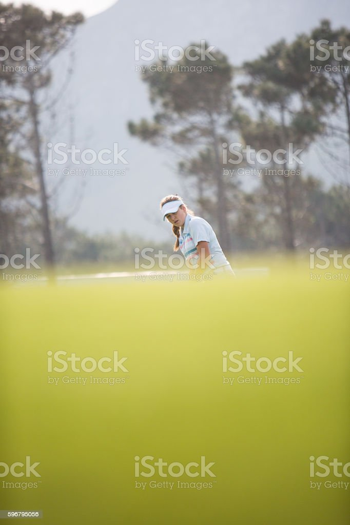 Young female golfer on the putting green stock photo