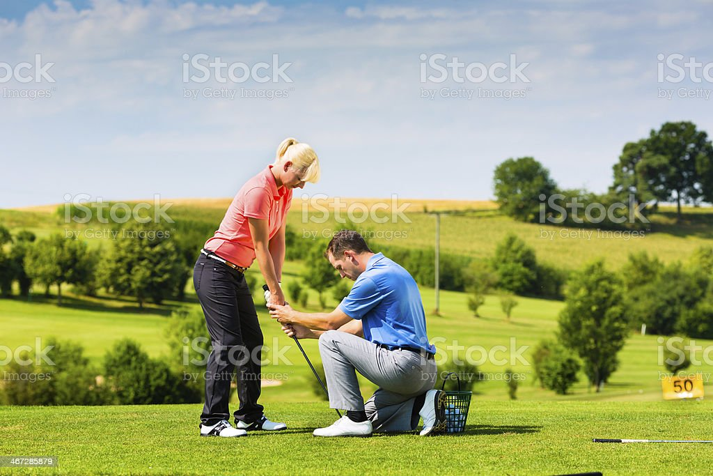 Young female golfer receives lessons on the tee box stock photo