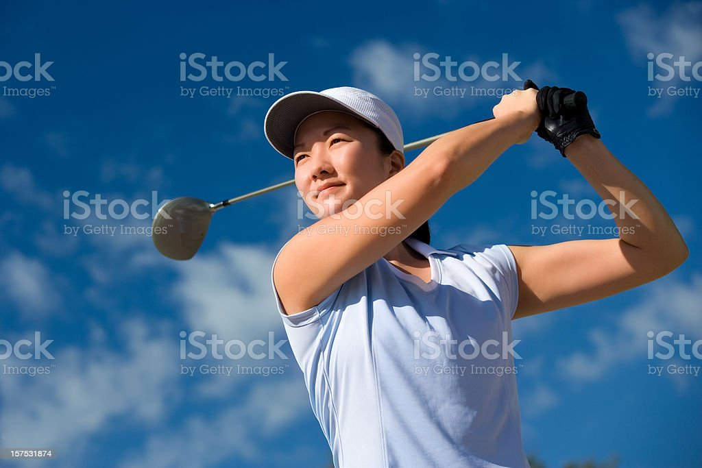 Young female golfer teeing off royalty-free stock photo