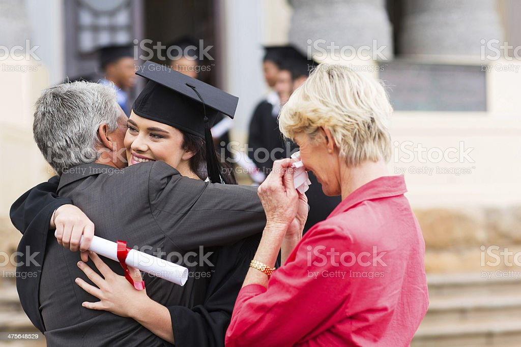 young female graduate hugging her father stock photo