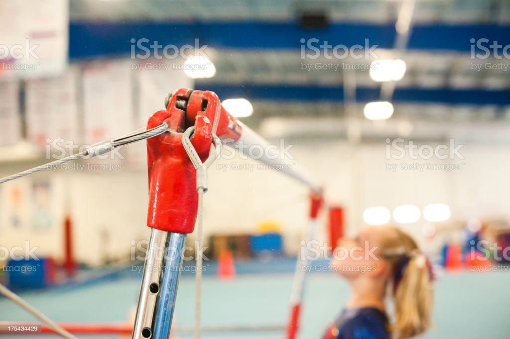 Young female gymnast on the uneven bars  stock photo