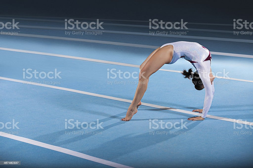 A young female gymnast posing in a bridge on a blue mat stock photo