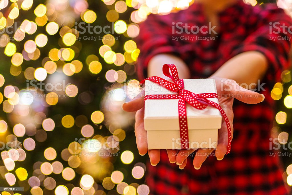 Young female hands holding christmas gift stock photo