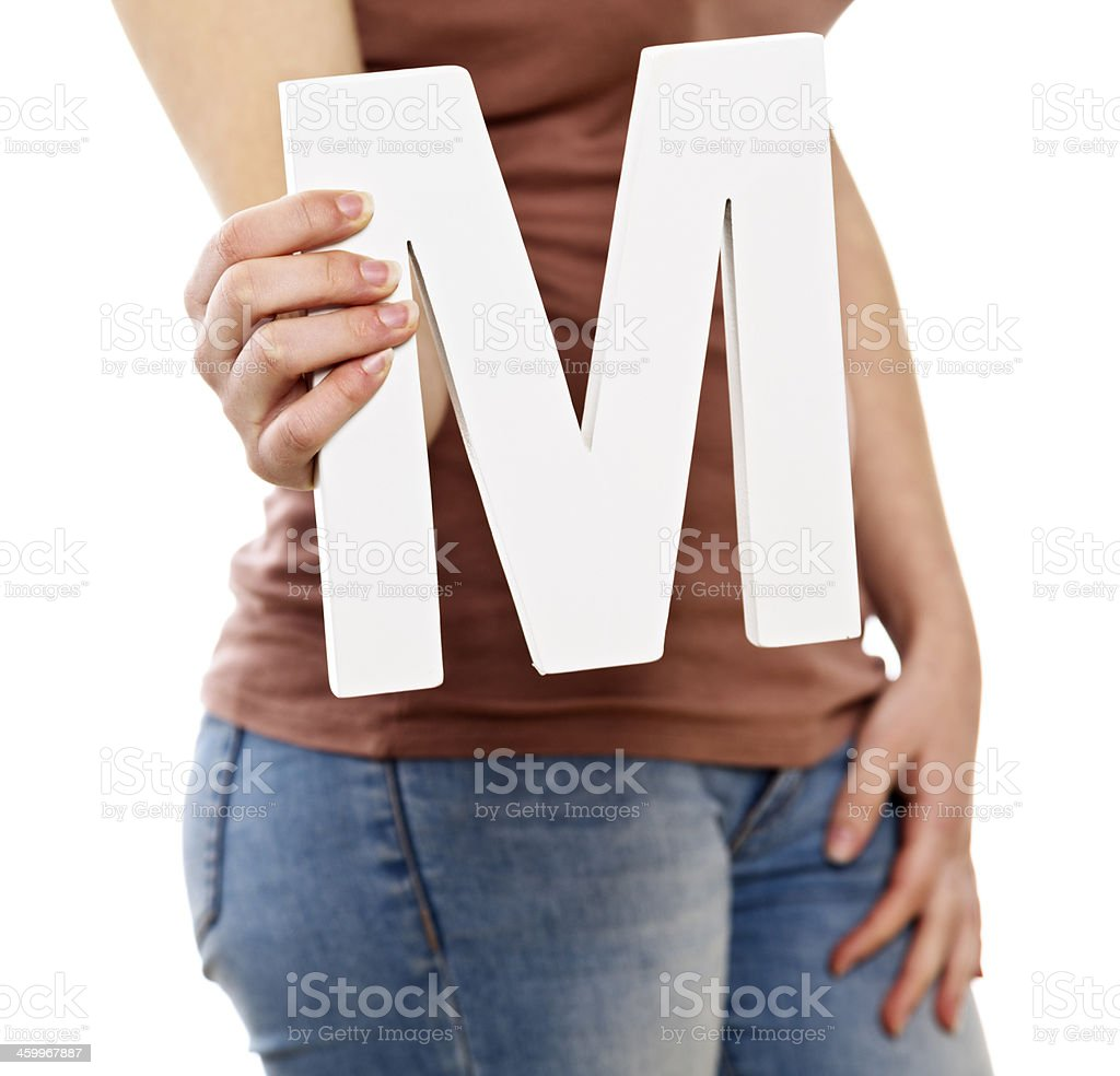young female hands holding large cut out letter m royalty free stock photo