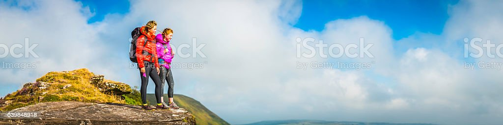 Young female hikers on mountain ridge overlooking summer cloudscape panorama stock photo