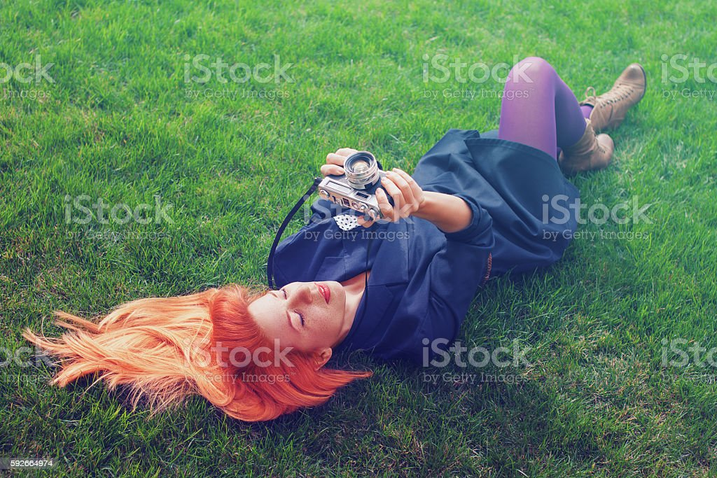 Young female hipster photographer lying on the grass stock photo