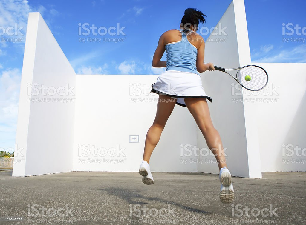 young female hitting tennis ball against a wall royalty-free stock photo