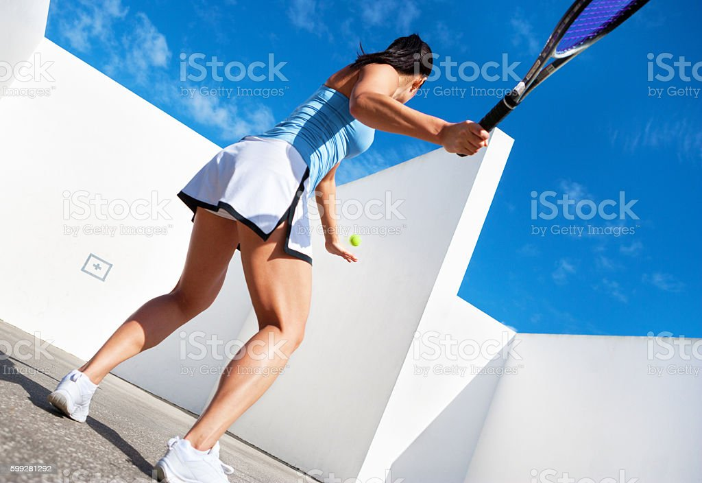 young female hitting tennis ball against a wall stock photo