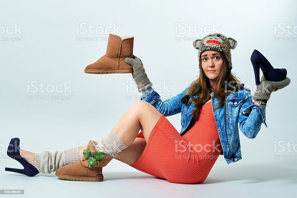 Young female holding a boot one hand and high heels stock photo