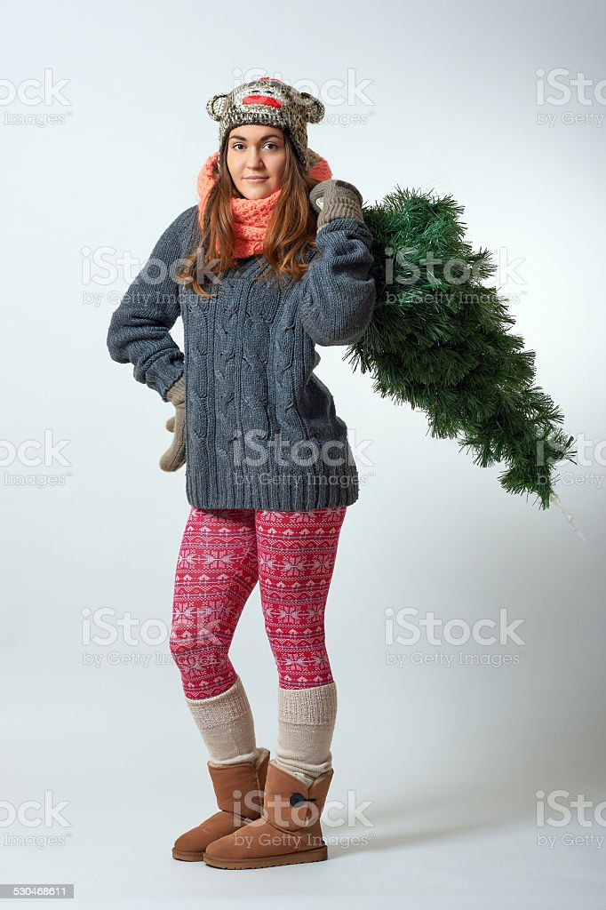 Young female holding a christmas tree in one hand stock photo