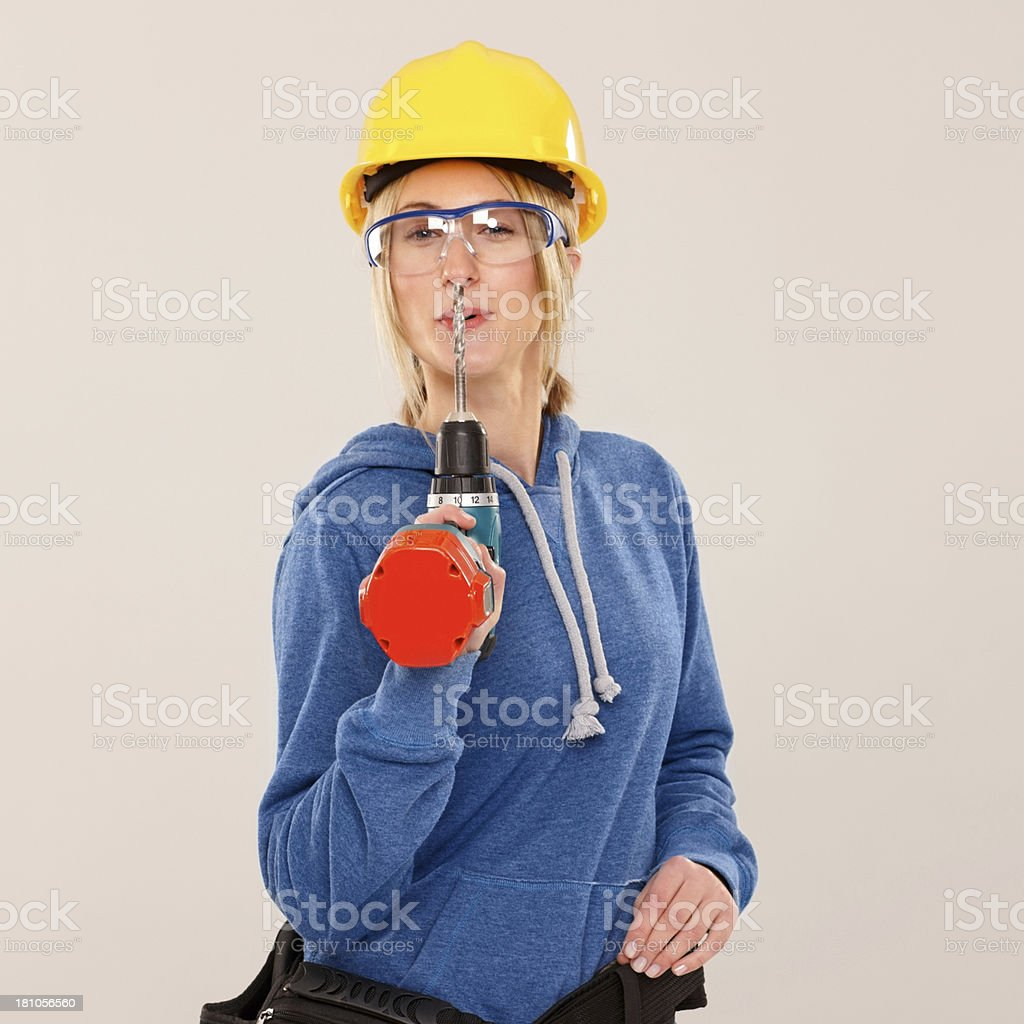 Young female holding a cordless electric drill on grey royalty-free stock photo