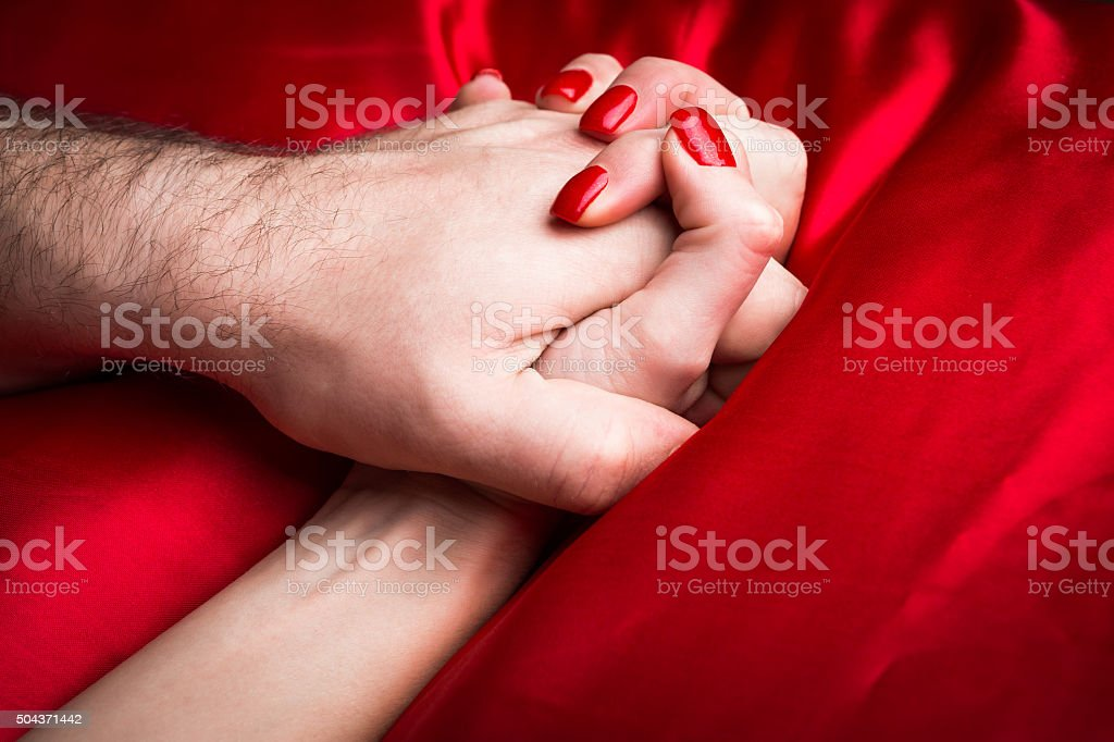 Young female holding hands sensually on red silk bed. stock photo