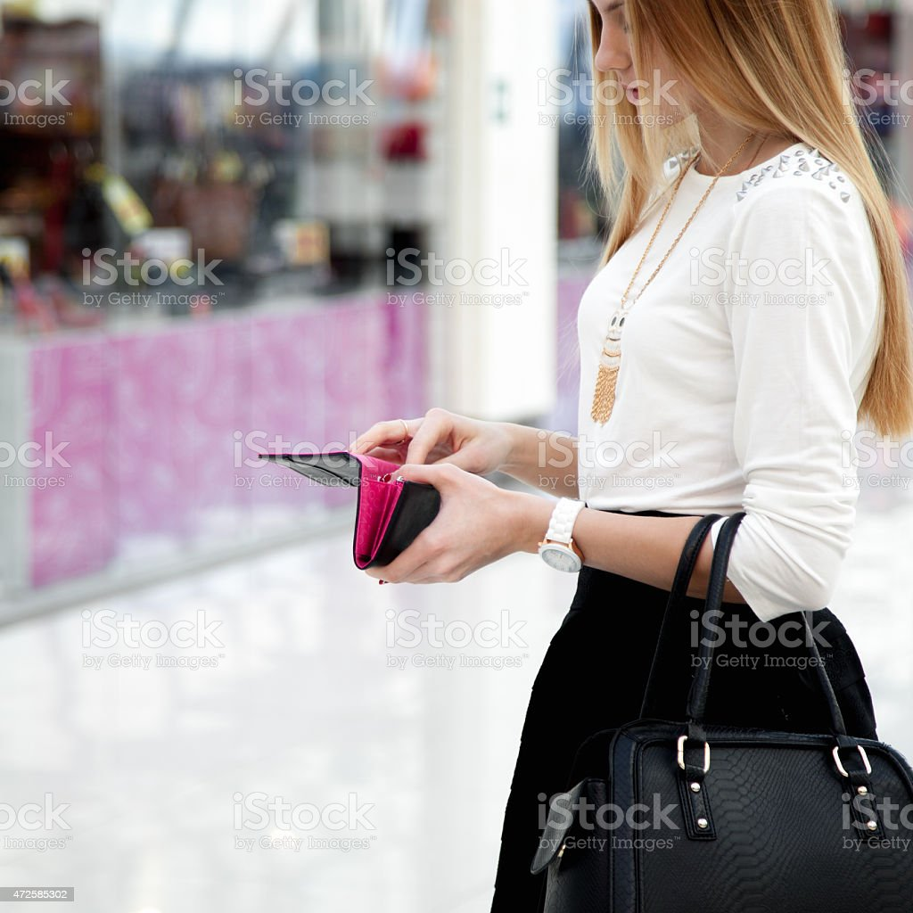 Young female in fashionable clothes looking into a wallet stock photo