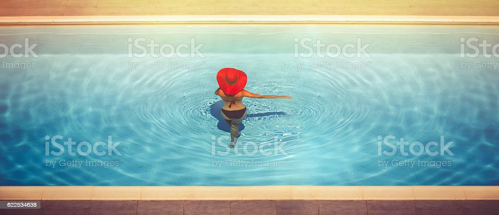 Young female in hats in the pool stock photo