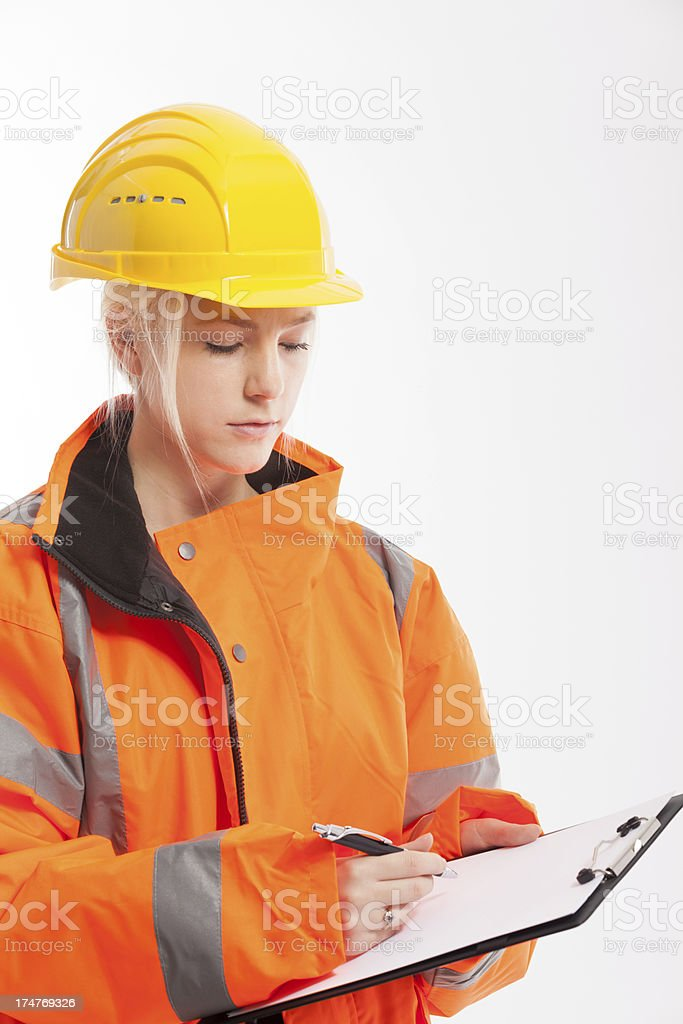 Young female industrial laborer taking notes stock photo