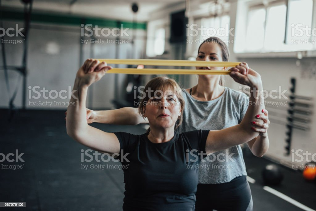 Young female instructor assisting her mother to strech resistance band stock photo
