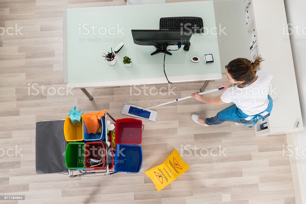 Young Female Janitor Mopping Wooden Floor stock photo