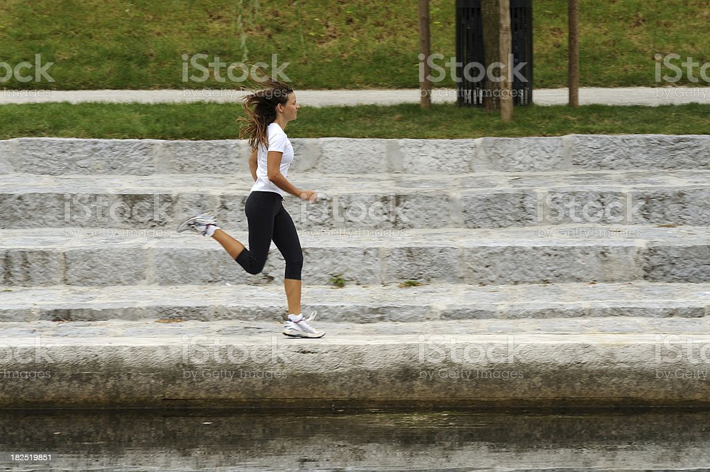 Young female jogging close to the river royalty-free stock photo