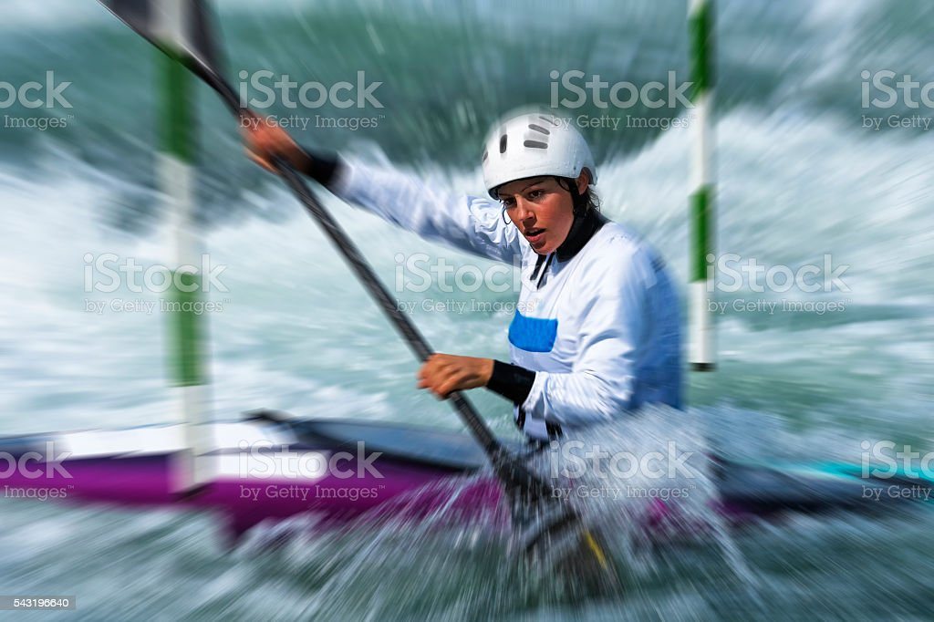 Young Female Kayaker at Slalom Race Passing the Green Gate stock photo